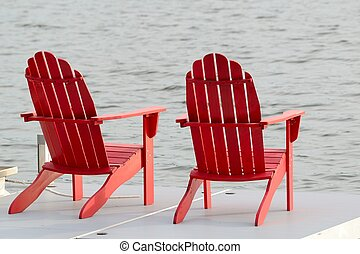 Two Red Adirondack Chairs on a Dock by the Lake