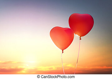 two red balloons in shape of heart on the background of...