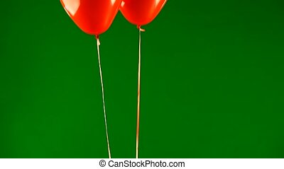 two red balloons in the form of heart raise a mail envelope...