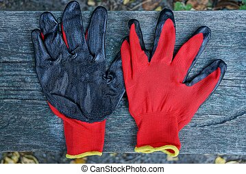 two red black construction gloves on a gray wooden board