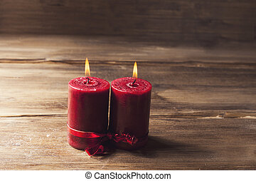 Two red candles tied with red ribbon, the symbol of Valentine's day, mimics the relationship of men and women, on wooden background from old boards