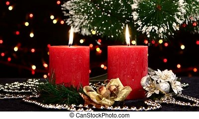 Two red candles with christmas decorations and tree on black, bokeh, light, garland, rotation