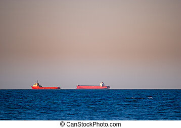 Two red cargo ships on the horizon at sunset, with blue sea and orange sky
