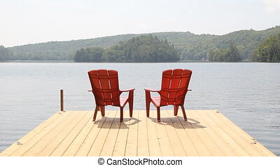 Two red chairs on cottage dock. - Two red chairs on a...