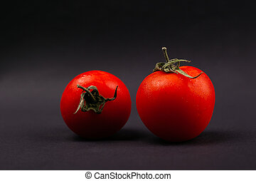 two red cherry tomatoes on a dark gray background