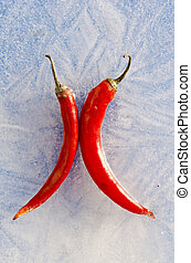 two red chilli peppers frozen in ice