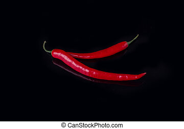 Two red chilli peppers on black background.