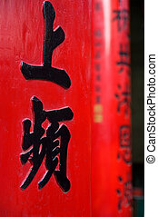 Chinese scripture, black characters on two columns at Chua Thien Hau Temple in Cho Lon, Ho Chi Minh City, Vietnam. The nearest column in focus, the second one blurred.