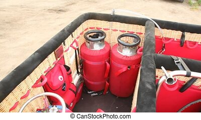 Two red cylinders with gas stand in balloon basket
