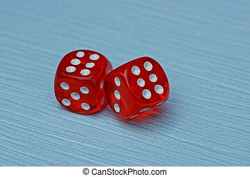 two red dice are on a blue table