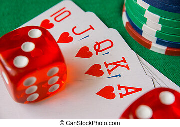 Two red dice, casino chips, flush royal cards on green felt