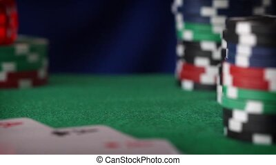 Two red dice rolls in hand, casino chips, cards on green felt