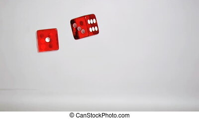Two red dices in super slow motion rebounding against a grey...