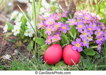 Two red Easter eggs in a garden