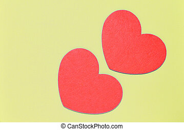 Two red felt hearts on a pale yellow background close-up. Flat lay, copy space. Valentine's Day greeting card