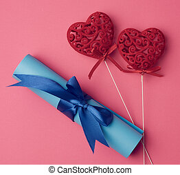 two red heart and roll of blue paper tied with a silk blue ribbon