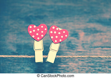 Two red heart on a background of wood. Creative heart - clothespins hanging on a rope. The Valentine's Day Holiday. Romantic photo in vintage style