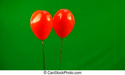 two red heart shaped balloons lift a mail envelope with a...