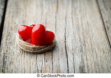 Two red heart-shaped on a wooden background.