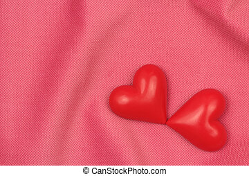 Two red hearts on a pink fabric background
