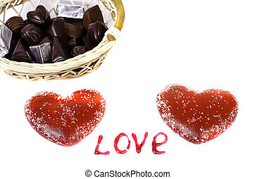 """Two red hearts on a white background basket with chocolate and the word """"Love""""."""