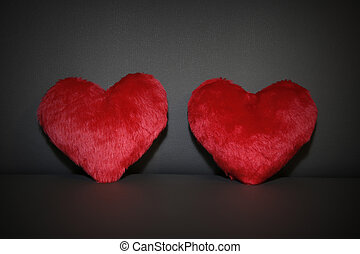 two red hearts on black background