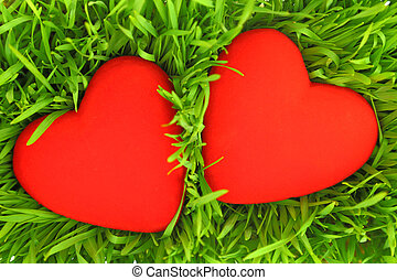 Two red hearts on green grass background