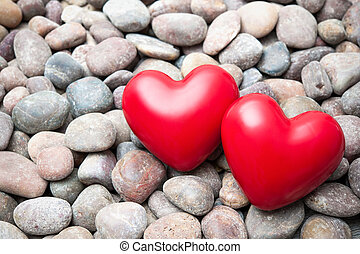 Two red hearts on pebble stones
