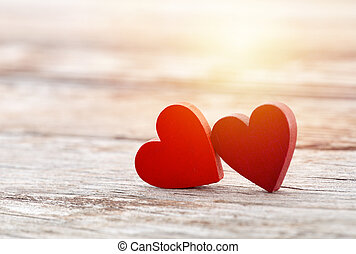 Two red hearts on wooden background in sunset