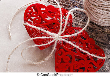 Two red hearts tied with a rope near a skein of thread