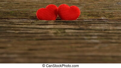 Two red hearts tuck on the wooden plank 4k