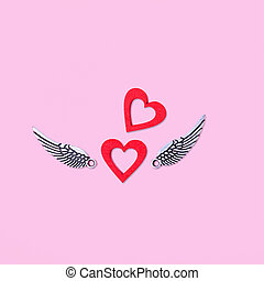 Two red hearts with silver wings on a pink background