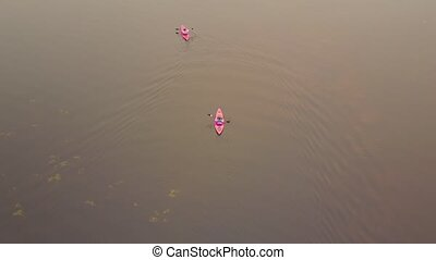 Two red kayaks on big lake with water lilies, Alberta,...