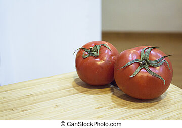 Two red ripe tomatoes on wooden cutting board