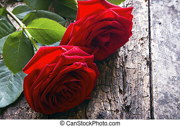 two red roses on a wooden background
