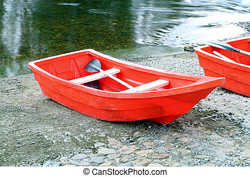 red rowboat - two red rowboat near the river