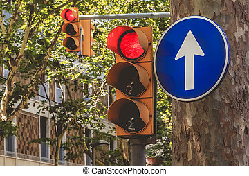 two red semaphore and a blue sign of obligation in street