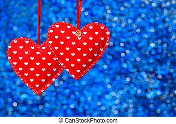 two red sewn hearts hanging against blue background