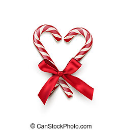 Two red striped candy cane in heart shape with red bow isolated on white background. Vector Christmas and New Year design element.
