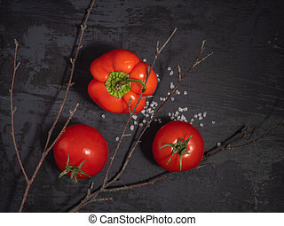 Two red tomatoes and peppers, a scattering of salt nearby, a dry twig of a tree, black background, top view