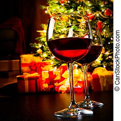 two red wine glasses against christmas tree background