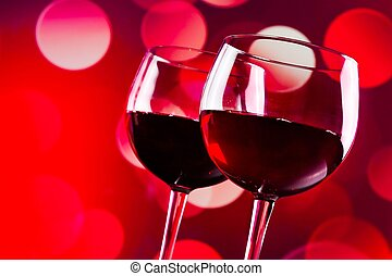 two red wine glasses against red bokeh lights background