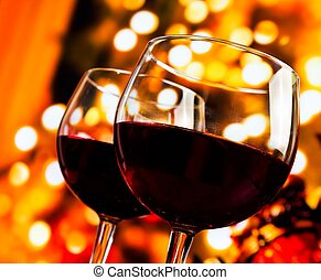 two red wine glasses against tree of bokeh lights background