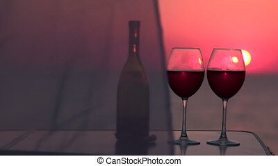 Two red wine glasses at sunset by the sea