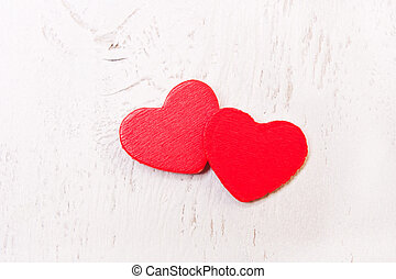 two red wooden heart on a white background