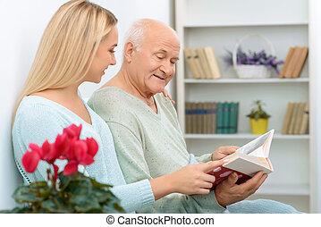 Two relatives looking through family album.