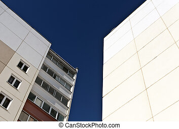 Two residential building and blue sky.