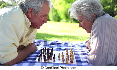Two retired people playing chess