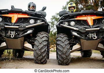 Two riders on quad bikes, front view, closeup
