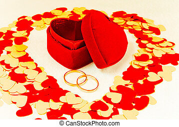 Two rings in front of a red heart shaped box